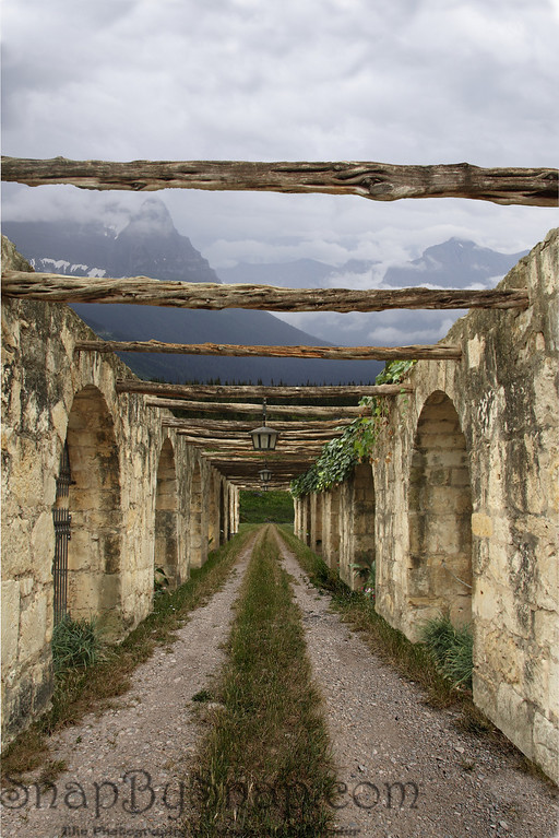 Pathway to the Mountains  This is actually a combination of three images.  The ground is from the plains of Montana.  The background and sky is from Glacier National Park.  The walls and wood beams are from the Alamo in Texas.